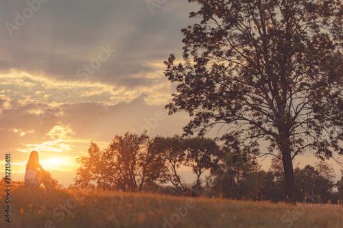 Fotografie, Obraz  Girl enjoying in the meadow at golden sunset time.