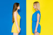 Female fashion models looking at each other isolated on blue and yellow background
