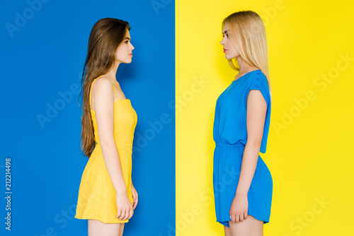 Photo Female fashion models looking at each other isolated on blue and yellow backgrou