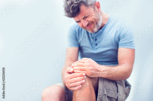Fotografiet  Closeup man hand holding knee with pain on bed, health care and medical concept