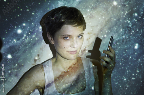 Portrait of woman, holding smartphone, projection of starry sky