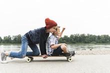 Happy Boys On Skateboard At The Riverside