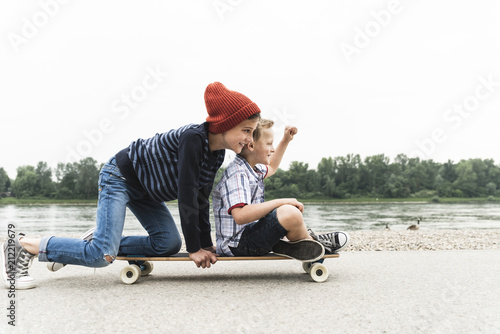 Happy boys on skateboard at the riverside