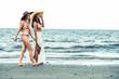 Happy women go sunbathing at sand beach in summer.