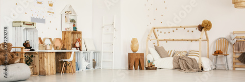 Obraz Panoramic photo of a child's bedroom interior with wooden furniture, house bed, stool and wall stickers - fototapety do salonu