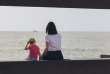 Mother With Little Daughter Looks At The Sea. Back View.