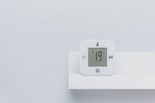 A White Digital Thermometer On The Shelf With Negative Space. Room Temperature Concept.