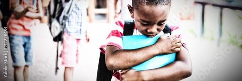 Photo  School friends bullying a sad boy in school corridor