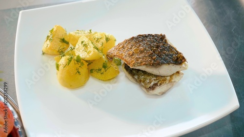 Deurstickers Klaar gerecht Dish of prepared potatoes with herbs and fish in white plate