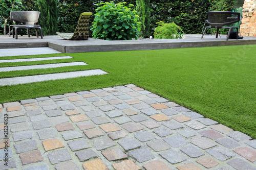 Foto op Aluminium Tuin Moderne Garten- und Terrassengestaltung: Materialmix aus Pflastersteinen, Betonsteinen, Holz und Kunstrasen
