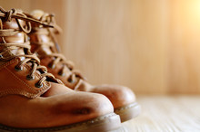 Yellow Leather Used Work Boots On Wooden Background Closeup. Place For Text