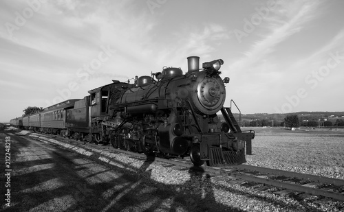 Steam train coming down tracks in a field in black and white