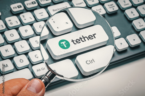 Fotografía  magnifying glass in hand focused on computer key with tether coin logo