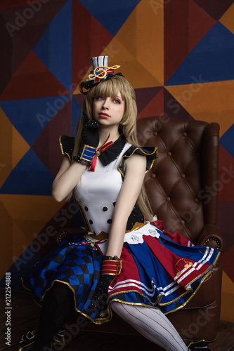 Obraz Cosplay of school idol / young cute beautiful girl anime cartoon sits on an armchair - fototapety do salonu
