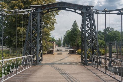 Fototapeta premium Najstarszy w Europie żelazny most wiszący na rzece Małej Panwi. Zbudowany w 1827 r. Przez Hutę Małapanew na podstawie projektu królewskiego inspektora stalowego Karla Schotteliusa. Ozimek, Opolskie Wojewoda