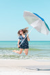 Young attractive fit woman, female, happy, smiling, jumping mid-air, in air on beach on sunny day with red sunglasses in Florida panhandle with ocean, holding umbrella
