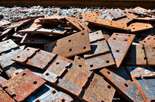 Pile Of Scrap Rail Railway Railroad Track Rusty Grungy Metal Plates Covered In Rust, Abandoned In Junk Yard With Grunge