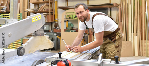 Tela friendly carpenter with ear protectors and working clothes working on a saw in t