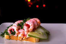 Shrimp Sandwich On A Plate With Lights In The Background