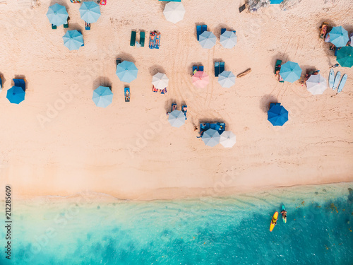 Fotografía  Top view of sandy beach with turquoise sea water and colorful blue umbrellas, ae