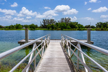 Ramp To Boat Dock On Blue Green Lake With Trees, Vegetation And Blue Sky - Vista View Park, Davie, Florida, USA