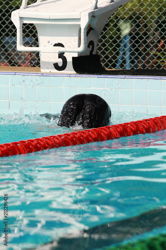 Swimmer swims and kick turn, flip turn in swimming pool at starting block number 3