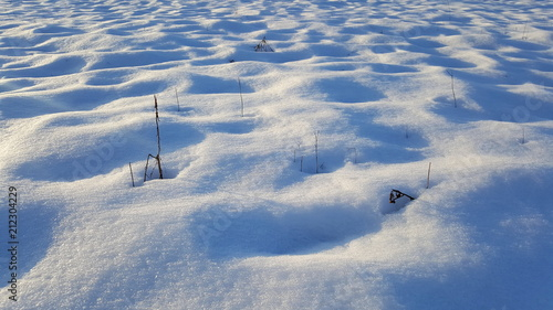 Windswept snow formations with small dried branches and grass sticking out at su Fototapet