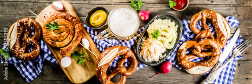 Fotografering Oktoberfest food menu, bavarian sausages with pretzels, mashed potato, sauerkrau