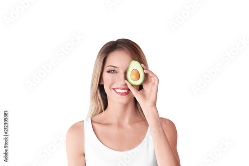 Portrait of young beautiful woman with ripe delicious avocado on white background
