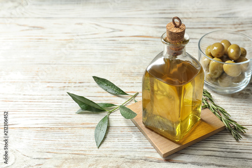 Bottle with fresh olive oil on table