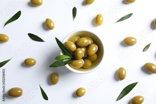 Flat lay composition with fresh olives in oil on white background