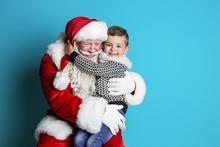 Little Boy Hugging Authentic Santa Claus On Color Background