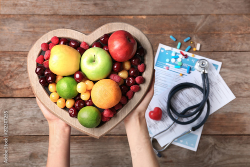 Female doctor holding plate with fresh fruits over wooden table, top view. Cardiac diet