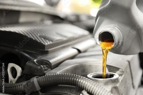 Fototapeta Pouring oil into car engine, closeup obraz