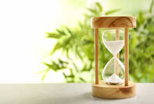 Hourglass With Flowing Sand On Table Against Blurred Background. Time Management