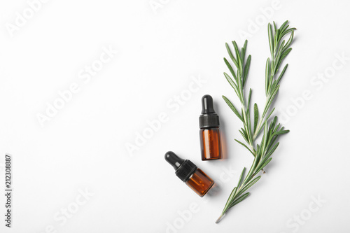Fototapeta Bottles of rosemary oil and fresh twigs on white background, top view obraz na płótnie