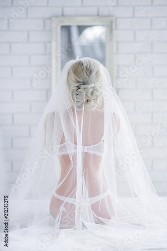 Beautiful bride in white lingerie sits on the bed hidden under the veil Canvas Print
