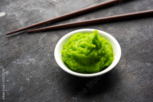 Photo Green wasabi sauce or paste in bowl, with chopsticks or spoon over plain colourful background