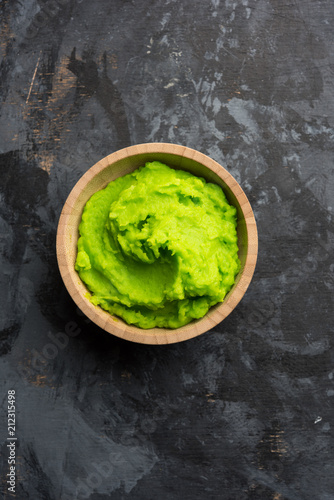 Fotografia Green wasabi sauce or paste in bowl, with chopsticks or spoon over plain colourful background