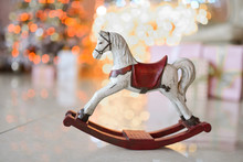 Little Wooden Toy Horse Stands On The Floor Before A Christmas Tree