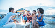 canvas print picture - Group of young tourist friends cheering with champagne at beach kiosk party