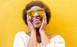 canvas print picture - Fashion african woman smiling and wearing sunglasses with yellow ochre background