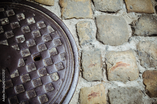 Lviv, Ukraine  Paving stone with metal canal hatch  The