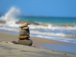 Stone turrets on the beach with waves in the background, concept of balance and harmony