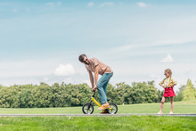 Father Riding Small Bicycle An...
