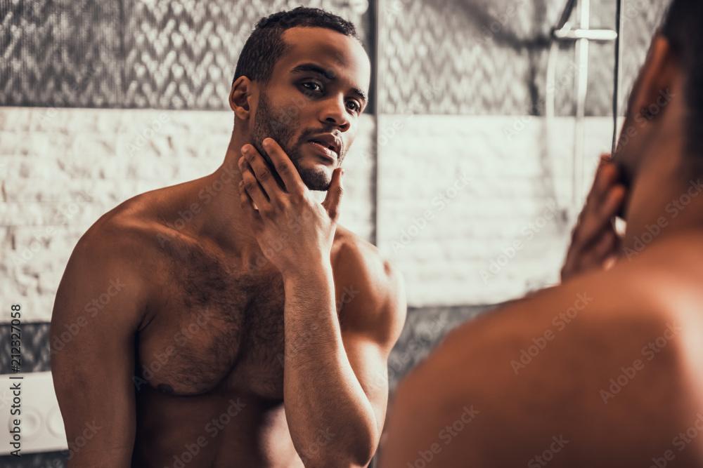 Fototapeta Afro-American Man Looking into Mirror in Bathroom.