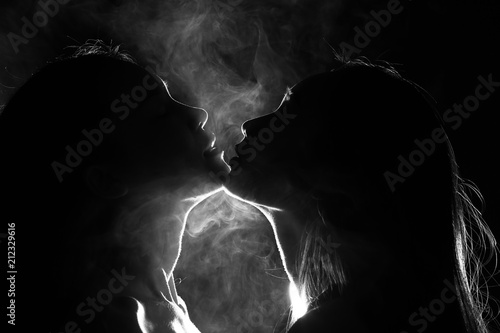Fototapeta Silhouette of two sexy woman kissing holding in darkness through light and smoke
