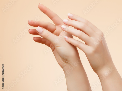 Beautiful Woman Hands. Female Hands Applying Cream, Lotion. Spa and Manicure concept. Female hands with french manicure. Soft skin, skincare concept. Hand Skin Care.