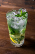 Classical mojito with lemon, soda, mint in glass on wooden background