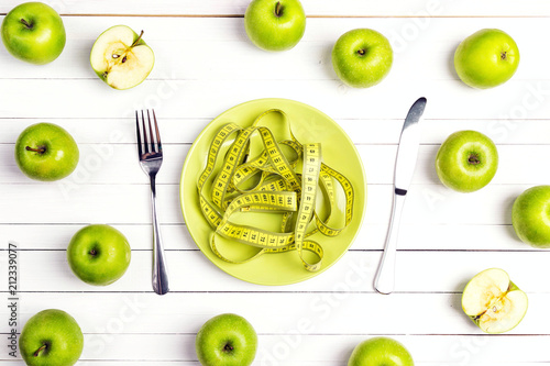 Fotomural  Diet concept table setting with cutlery, yellow measuring tape instead food and green apples on white wooden table